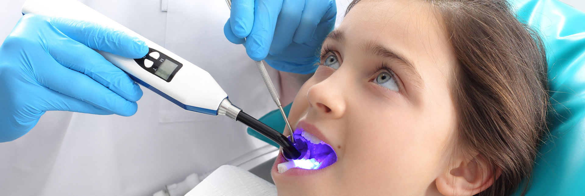 A dentist doing laser treatments to young girl